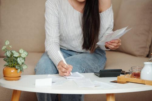 海外移住予定の女性が確定申告や住民票について調べている図